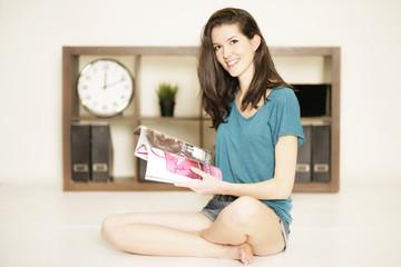 Mädchen liest zu Hause Zeitung