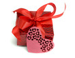 Red gift tied up by a bow and a card heart