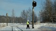 Railroad worker  with cell phone near  signal beacons pole