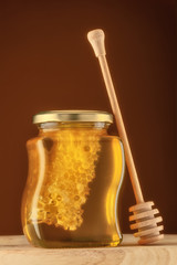 Glass of honey with honeycomb