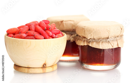 ripe barberries in wooden bowl and jars of jam isolated white