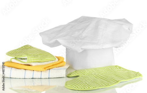 Chef's hat with kitchen towels and potholders isolated on white