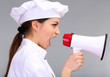 Portrait of young woman chef with megaphone on grey background