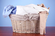 Bright clothes in laundry basket,on color background