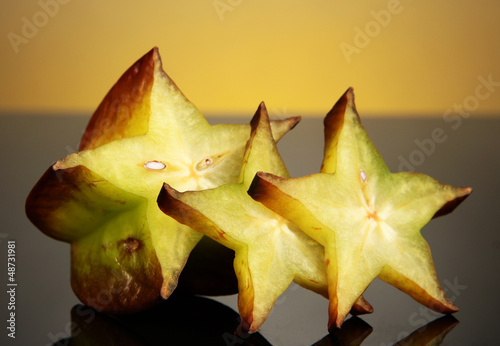 Two ripe carambolas on yellow background