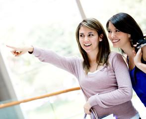 Shopping women pointing away