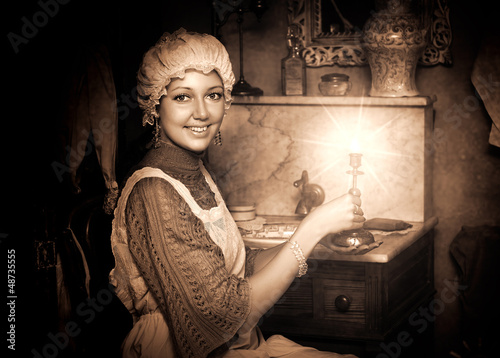 woman in old cap with candlestick