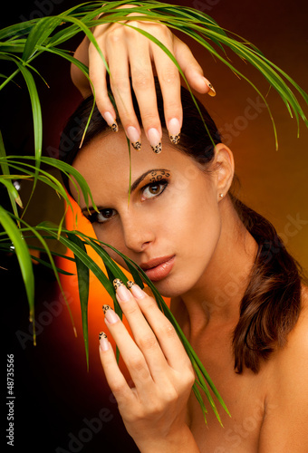 tanned woman with long acrylic leopard nails and makeup