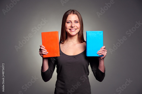 happy young woman showing two books