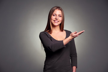 young woman pointing palm up