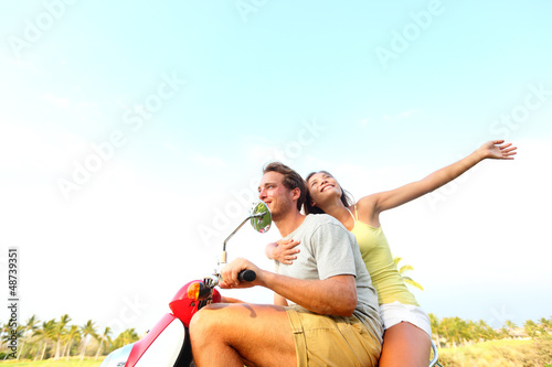 Young happy free couple in love on scooter