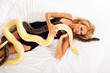sexy young woman lying on bed with two pythons