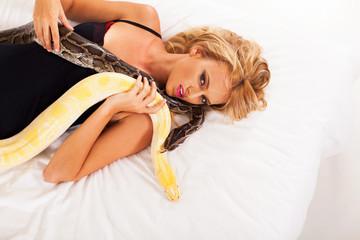 gorgeous young woman lying on bed with two pythons