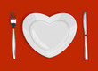 plate in shape of heart, table knife and fork on red background - 48743366