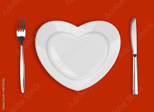 plate in shape of heart, table knife and fork on red background