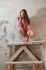 Young woman sitting on decorator's table