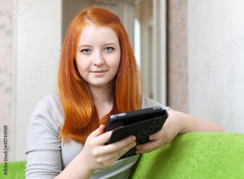Teen girl reads e-reader or tablet computer