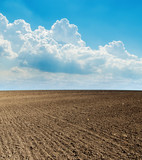 blue cloudy sky and black plowed field