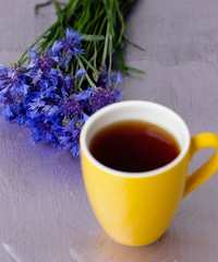 Yellow cup of tea and a bouquet cornflowers