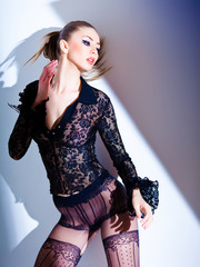 sexy model dressed in lace blouse and elegant tights posing