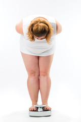 Obese young woman standing on a scale