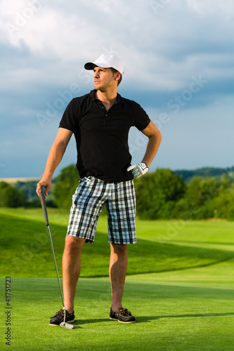 Young sportive man playing golf on a course