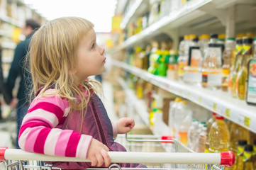 Adorable girl in shopping cart selecting sunflower oil in superm