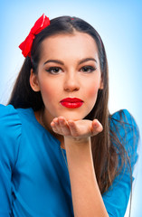 Portrait of a beautiful woman in blue sending kisses