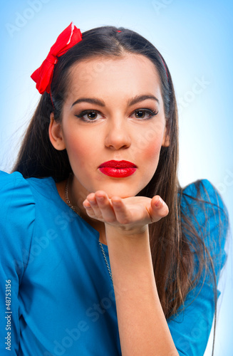 Portrait of a beautiful woman in blue sending kisses