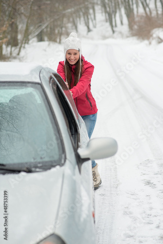 The girl is pushing a broken car on the road in winter