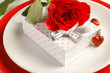 Romantic dinner setting with a rose and gift box