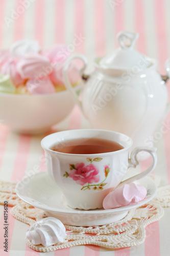 Black tea in elegant cup with  meringue cookies