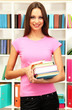 Young attractive female student holding her school books in