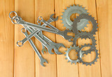 Metal cogwheels and spanners on wooden background