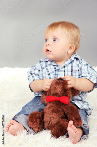 Little boy sitting on white carpet on gray background