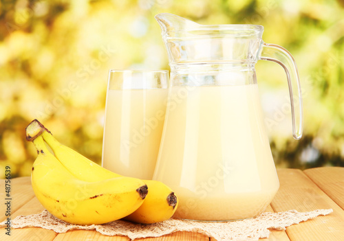 Full glass and jug of banana juice and bananas