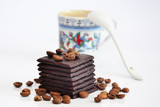 Chocolate with coffee beans and unfocused cup of coffee