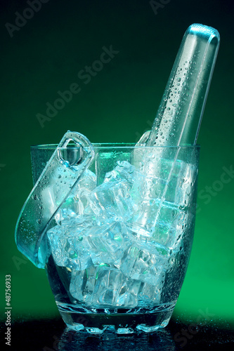Glass ice bucket on dark green background