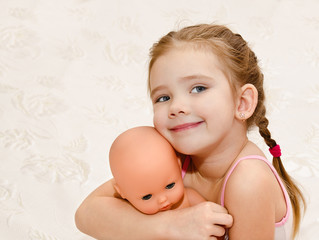 Cute smiling little girl with baby doll
