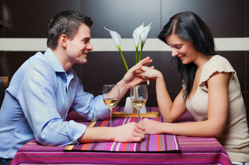 Young couple sitting in restaurant and flirting