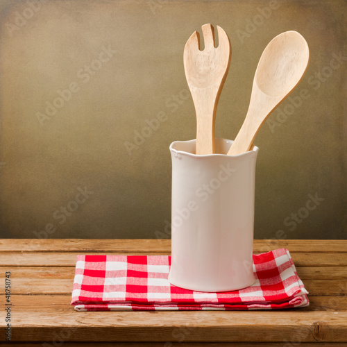 Kitchen utensils with tablecloth on wooden table