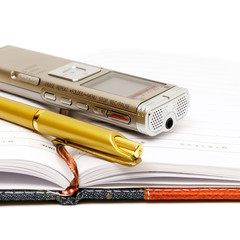 Dictaphone, notepad and ballpen isolated on white background