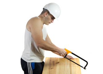 Helmeted young worker cutting a wooden board with a saw
