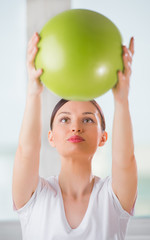 Portrait of fit and healthy woman with toning ball at fitness cl