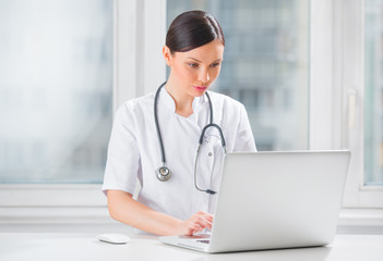 Portrait of a female doctor using her laptop computer at clinic