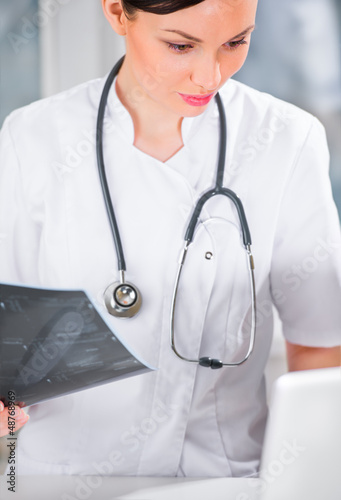 Portrait of a female doctor holding ultrasound results and using