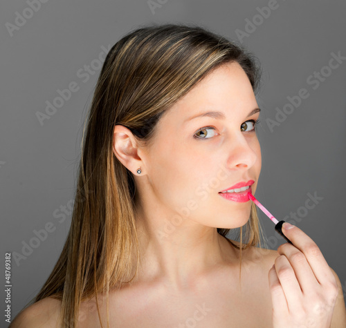 Attractive woman applying gloss on her lips