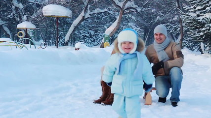 Young family with their baby in a winter park (SLOW)
