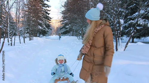 Young mother running, and ride your child on a sled