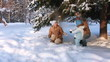 Young parents with a child playing in a winter forest (SLOW)